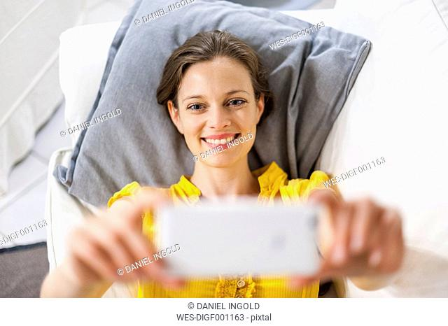 Woman lying on couch taking selfie