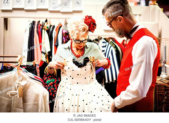 Quirky vintage woman trying dress in antique and vintage emporium