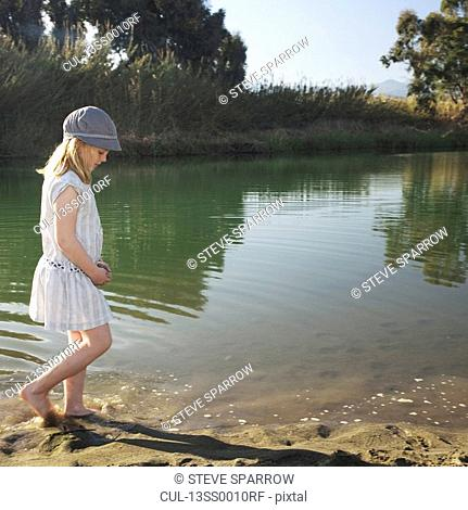 Young girl by river with feet in water
