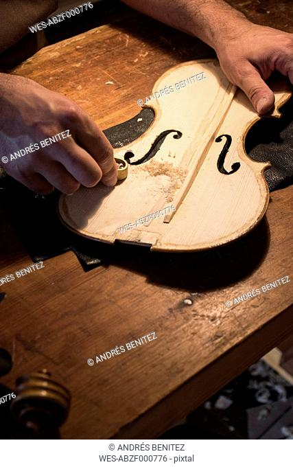 Luthier using a mini hand plane on the top plate of a violin in his workshop