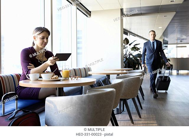 Businesswoman using digital tablet at breakfast table in airport lounge