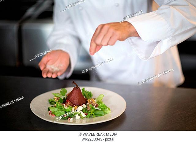 Chef seasoning salad on counter