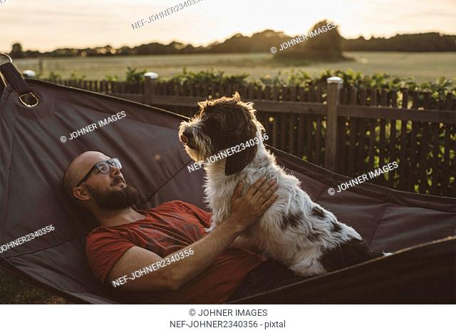 Young man relaxing in hammock with dog