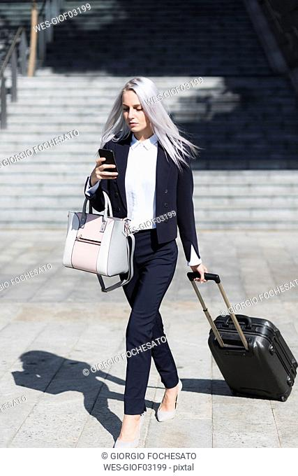 Young businesswoman on the go in the city checking cell phone