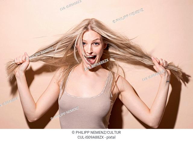 Portrait of young blonde woman holding hair and screaming