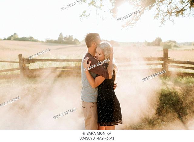 Romantic man and girlfriend hugging on dusty dirt track at sunset