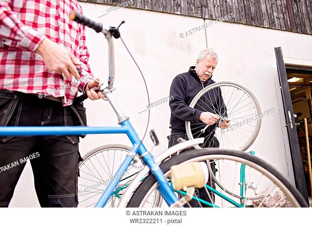 Father and son repairing bicycles outside workshop