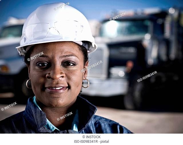 Portrait of female worker in hard hat in front of recycling plant trucks