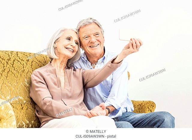 Senior couple relaxing at home, taking self portrait using smartphone