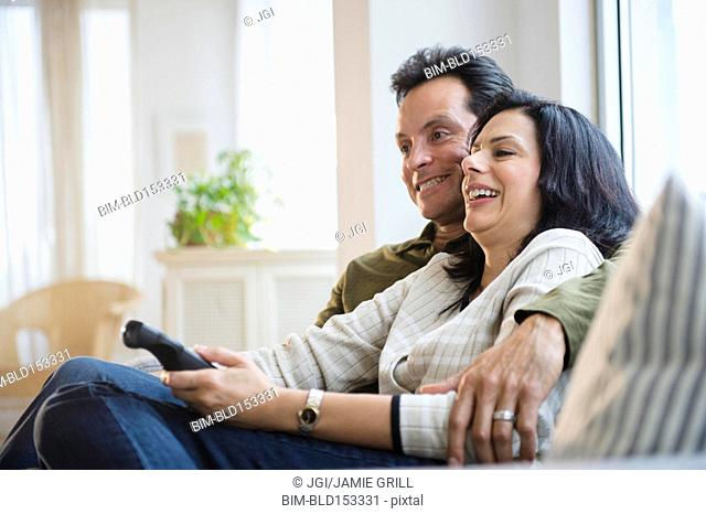 Couple watching television on sofa in living room
