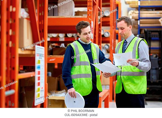 Manager training factory worker in factory warehouse