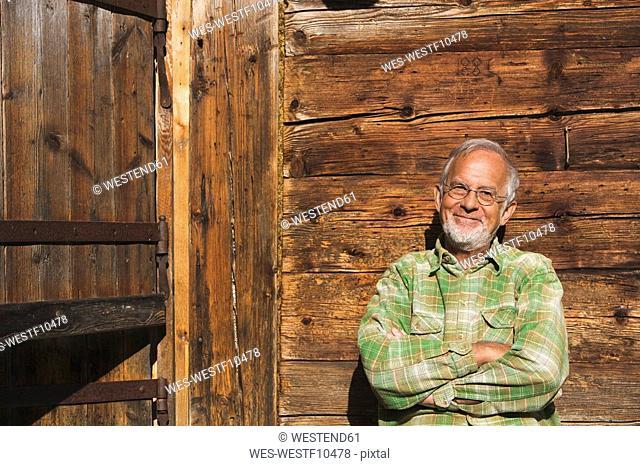 Austria, Senior man, arms crossed, smiling, portrait