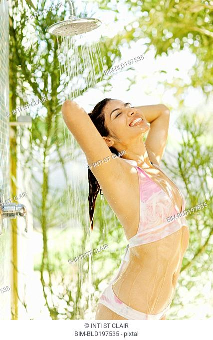 Hispanic woman showering outdoors