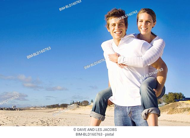 Caucasian man carrying girlfriend piggyback on beach