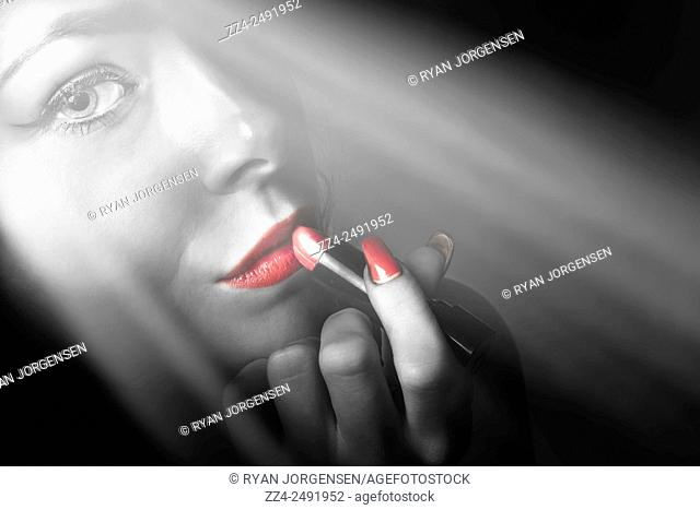 Black and white beauty portrait on the face of a trendy fashion model with long lashes and red nail polish manicure applying matching lipstick makeup