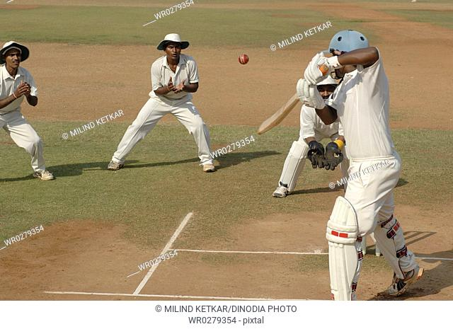 Slip fielder about to catch red ball off the bat of the batsman on pitch in cricket match MR705H,705I,705J,705K