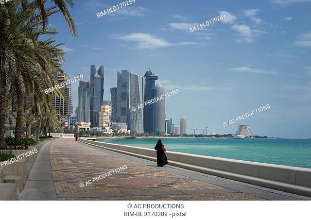 Woman walking on Doha waterfront, Doha, Qatar