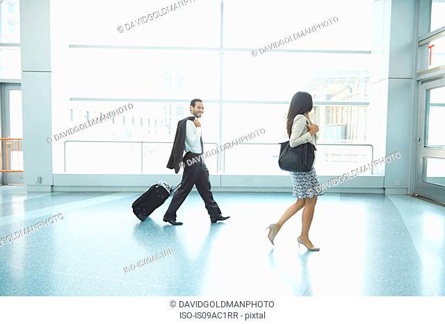 Businesspeople walking through Staten Island Ferry terminal pulling wheeled suitcase