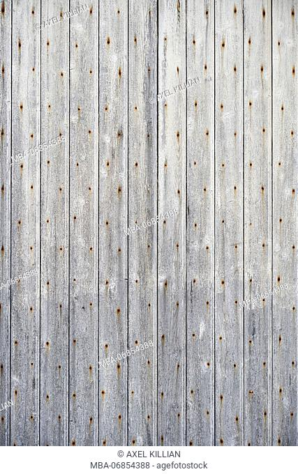 Wooden boards of a door with rusty nails