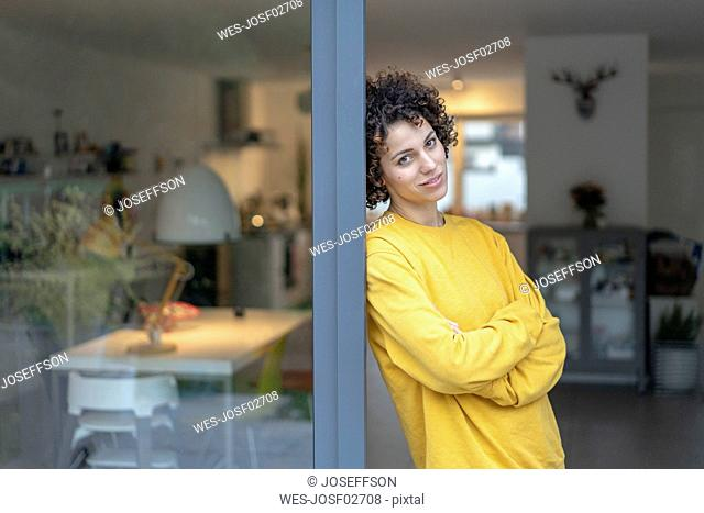 Portrait of woman leaning against terrace door at home