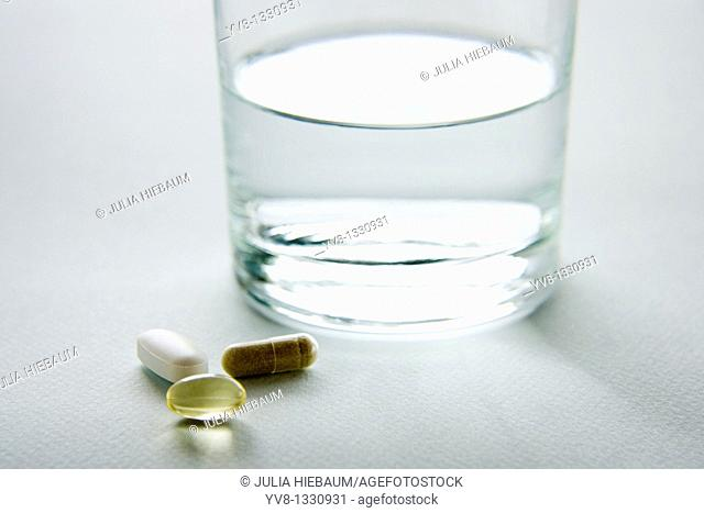 Various vitamins with a glass of water