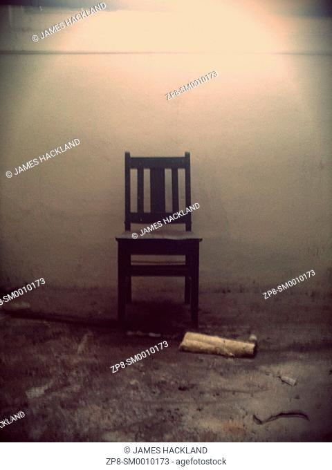A single wooden chair sits amongst debris in an abandoned psychiatric hospital in Ontario, Canada