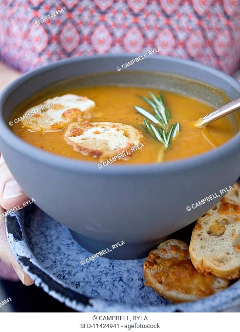 A woman holding a bowl of roasted vegetable soup with rosemary and cheese crostini