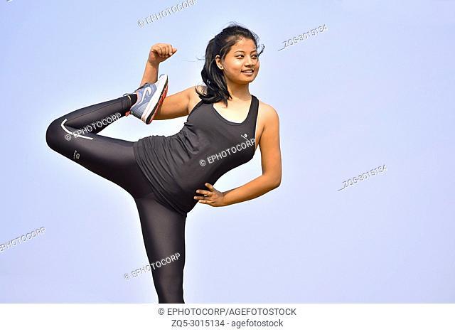 Young Indian girl doing fitness exercise. Mountain backdrop, Pune, Maharashtra