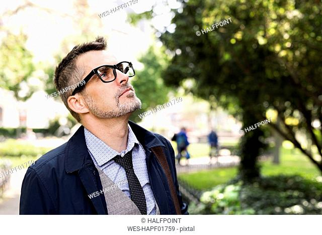 Mature businessman in city park looking up