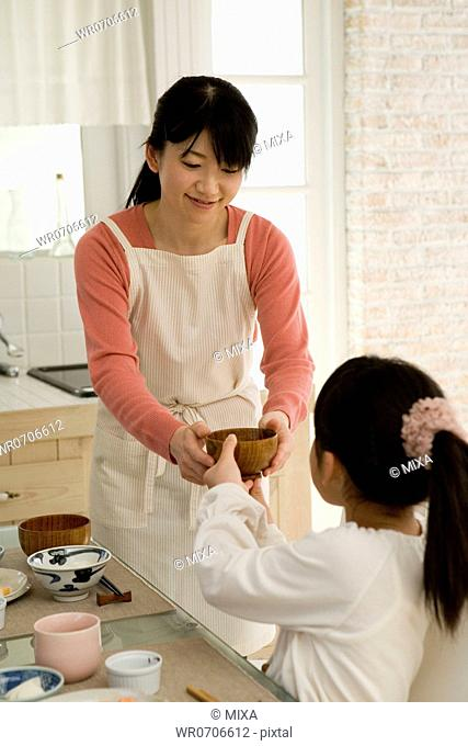 Daughter handing bowl to mother for refill