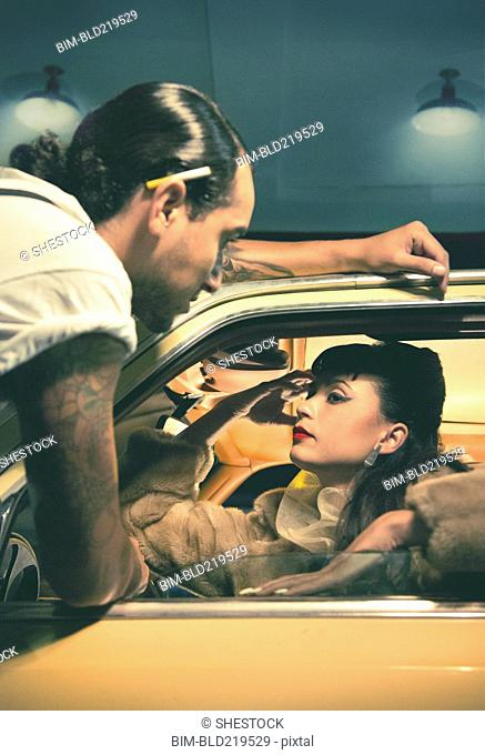 Glamorous couple talking in vintage car