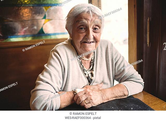 Portrait of smiling senior woman sitting in a restaurant