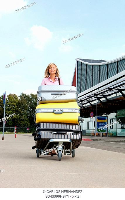 Mid adult woman pushing luggage trolley to airport