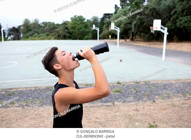 Male teenage basketball player drinking from water bottle on basketball court