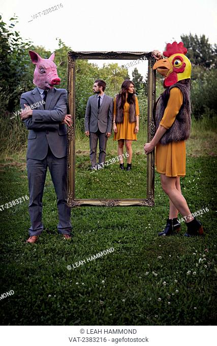 A couple standing together inside a frame being held by themselves in animal masks; Edmonton, Alberta, Canada
