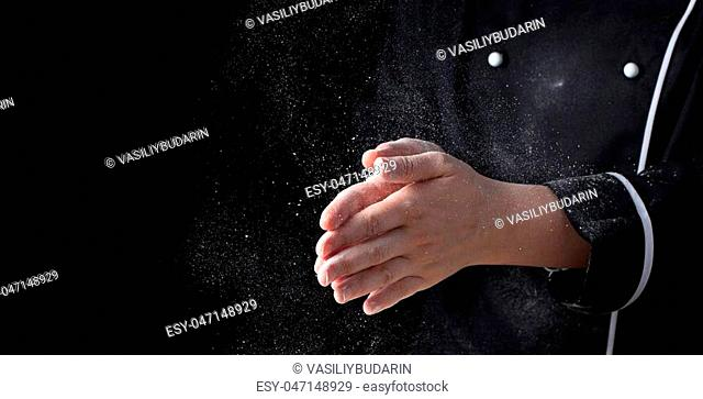 Chef hands in flour on black background banner. Making pizza, pasta, baking bread and sweets. Clap with splash of white flour with copy space