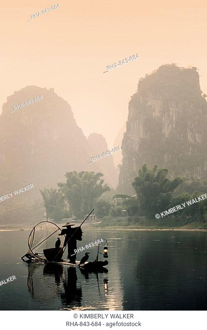 Silhouette of a cormorant fisherman paddling a lantern lit bamboo raft at sunrise on the Li River, China, Asia