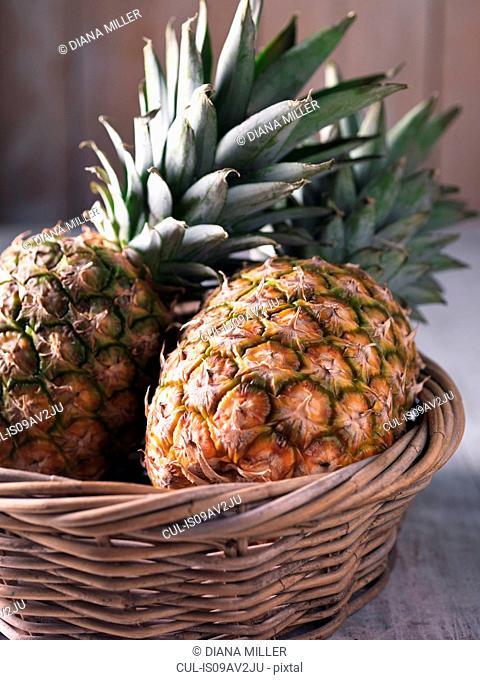 Two fresh pineapples in wicker basket