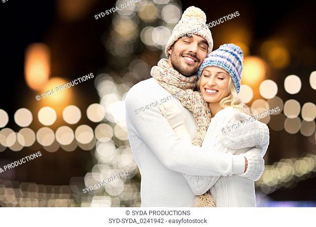 happy couple hugging over christmas lights