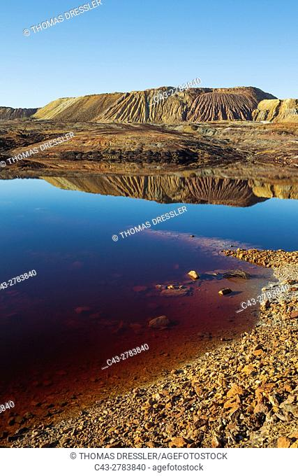 Dramatic landscape of mineral-rich ground and rock, scarred by the open-cast mineworkings of the Rio Tinto mines at the town of Minas de Riotinto and rainwater...