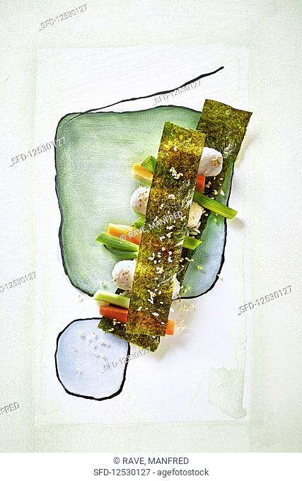 Sushi with vegetables and nori leaves on a painted surface