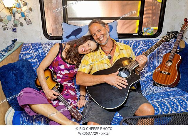 Man and woman cuddling on sofa in camper with guitars
