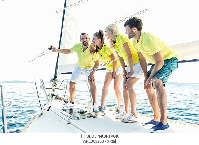 Group of friends taking pictures on sailboat, Adriatic Sea