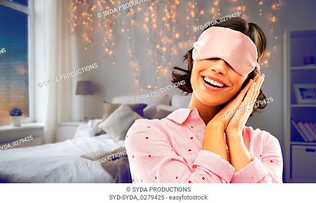 happy young woman in pajama and eye sleeping mask