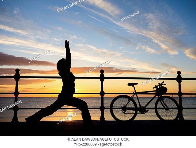 Female mountain biker stretching at sunrise at Seaton Carew near Hartlepool, north east England, United Kingdom