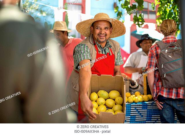 Market trader enticing shoppers to buy lemon