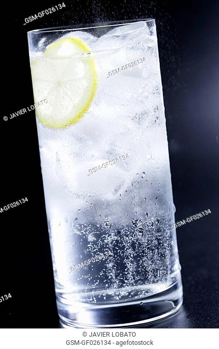 Tall glass with soda water in black ground
