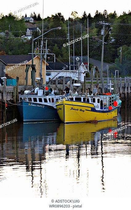 Two salt water lobster fishing boats moored in a safe harbour being made ready for the days work