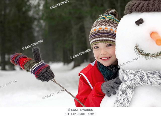 Close up of smiling boy behind snowman
