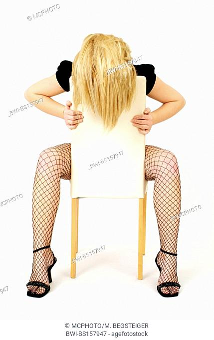 model in fish-net stockings and high heels posing on a chair